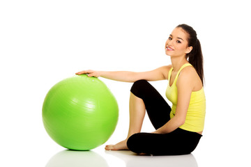 Young woman exercising with pilates ball.