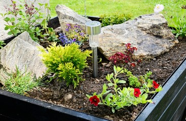 Ornamental flowerpot with flowers, stones and solar lamp.