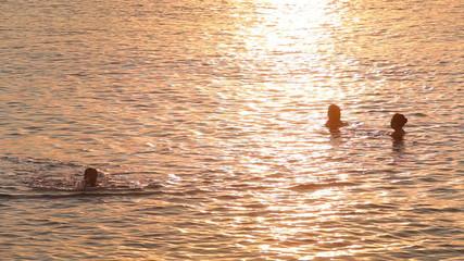 people swim in sea against sunlight