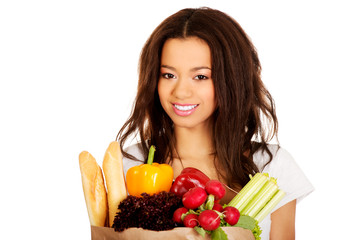 Young woman with grocery and vegetables.