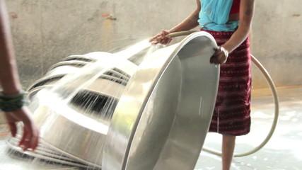 Indian women wash large metal pots