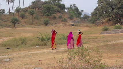 Indian women with children are on a rural road