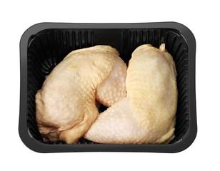 Raw chicken legs in black tray