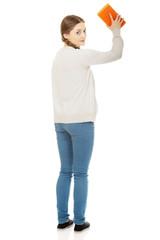 Teen woman with kitchen sponge.