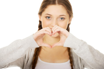 Teenager making heart shape with hands.