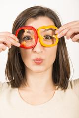 Woman looking through sliced bell pepper like eye glasses