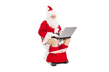 Santa Claus sitting on a toilet and working with laptop