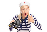 Surprised female sailor holding binoculars