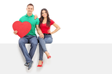 Man holding heart seated on panel with his girlfriend