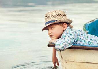 Boy in straw hat lying in old boat