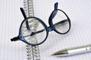 Lunettes et stylo posés sur un cahier à spirales