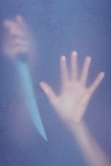 Hand touching frosted glass and holding knife