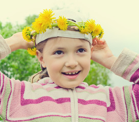 the young girl tries on a wreath from yellow flowers