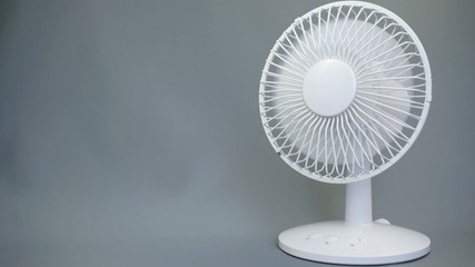 Rotating electric fan on gray background