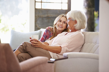 Grandmother With Adult Granddaughter Relaxing On Sofa