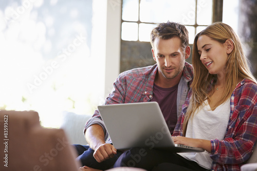Couple At Home In Lounge Using Laptop Computer