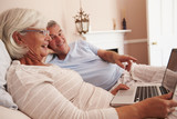 Senior Couple Lying In Bed Looking At Laptop Computer