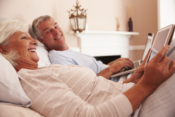 Senior Couple Lying In Bed Using Digital Devices