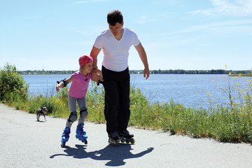 Dad teaches little daughter to roller skate