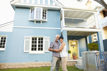 Portrait Of Mature Couple Standing Outside Beautiful House