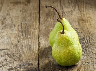 Two fresh green pear with drops of water on wooden table, select