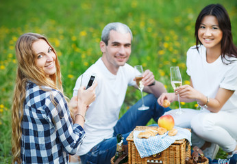 Happy smiling friends drinking champagne on picnic