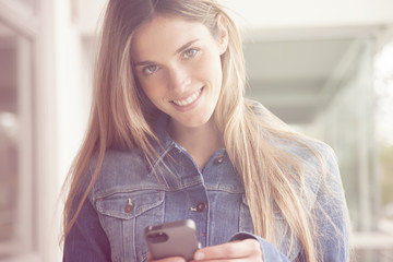 Happy young woman with mobile phone, sending text message