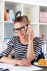 Young woman consulting customer on phone sitting at the desk