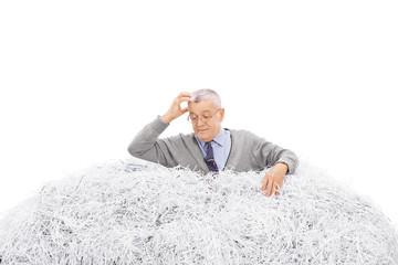 Confused senior looking in pile of shredded paper