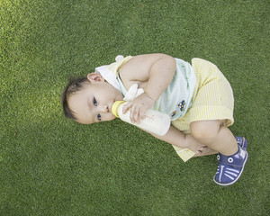 Asian baby boy laying on the grass field and  drinking milk