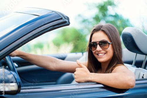 Leinwandbild Motiv Cute girl in convertible doing thumbs up.