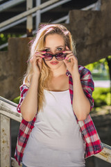 Trendy hipster girl standing on stairs looking over sunglasses