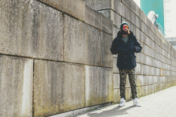Man in Winter Outfit Standing Beside Concrete Wall