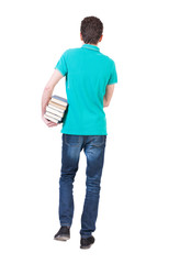 Back view of going  handsome man carries a stack of books.