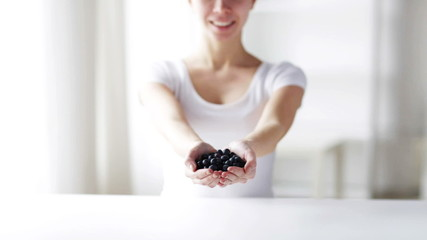 close up of young woman showing blueberries