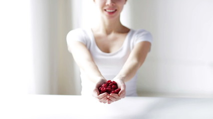close up of young woman showing raspberries