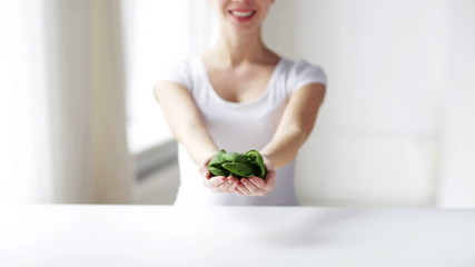 close up of young woman showing spinach