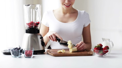 smiling young woman with blender chopping banana
