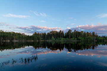 Вечер на озере с отражением леса в воде, Россия, Урал