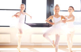 Fototapety Group of young ballerinas practicing pirouettes