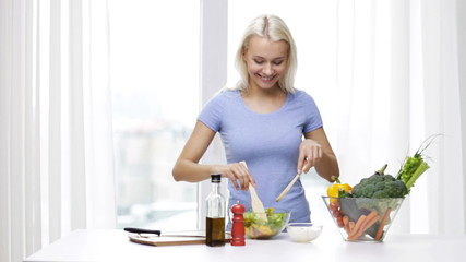 smiling woman cooking vegetable salad at home