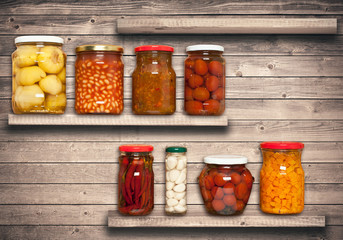 Preserved carrots, tomatoes, garlic, chilli, beans on shelf near