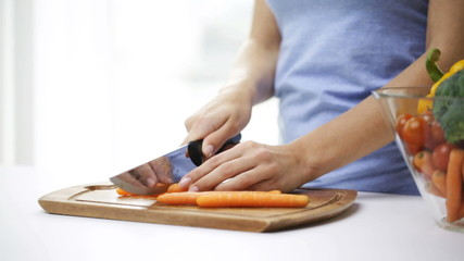 close up of young woman chopping carrot at home
