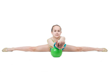 Little girl gymnast sits on split with green ball
