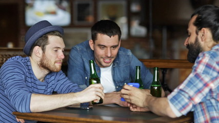 male friends with smartphones drinking beer at bar