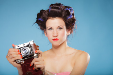 girl in hair curlers taking picture with old camera