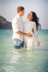 bride and groom hug in sea