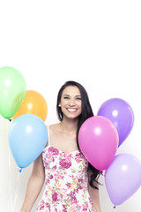 Smiling Young Pretty Brunette Woman holding Colorful Balloons