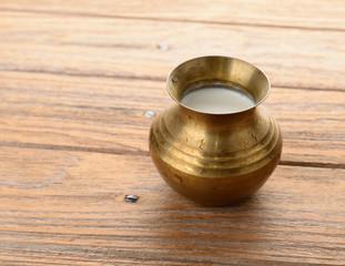 a brass pot of milk on wood texture