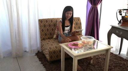 Young woman sit on sofa using tablet and eating snack and fruit